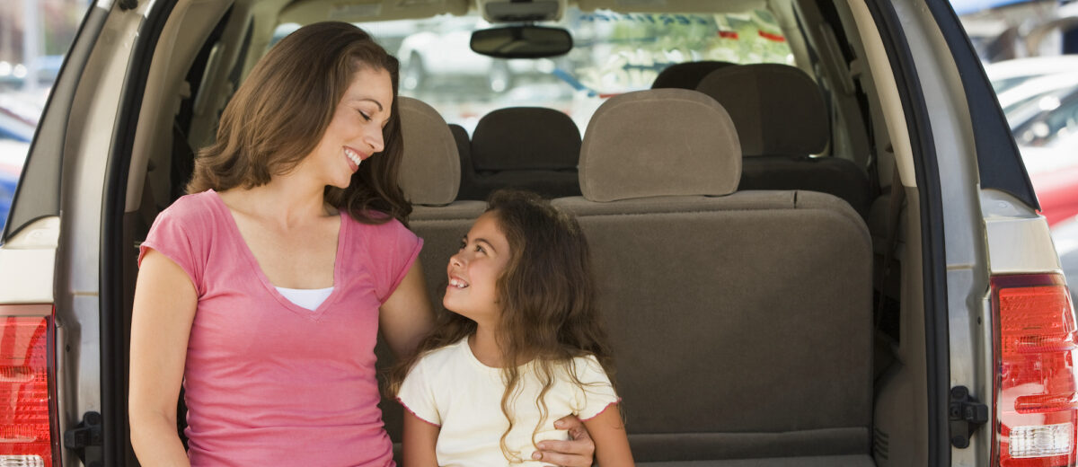 Woman with young girl sitting in back of van smiling. Mother and daughter looking at each other.